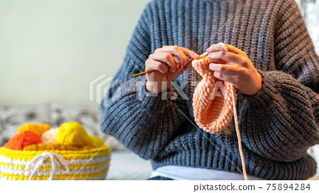 Woman knitting on the bed 75894284