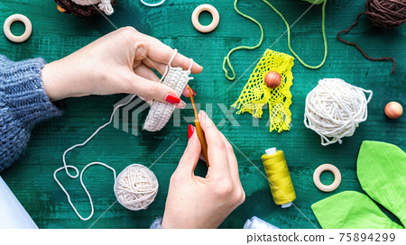 Woman is knitting using hooks and white yarn 75894299