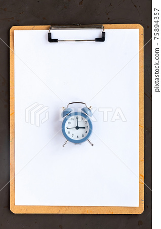 Notepad with paper and alarm clock 75894357