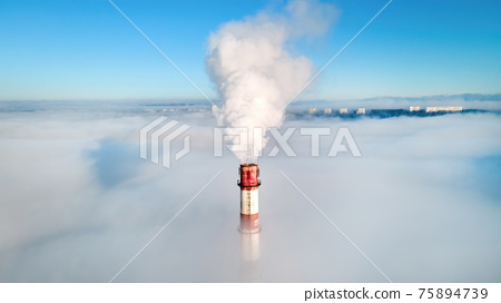 Aerial view of thermal station's tube visible above the clouds 75894739