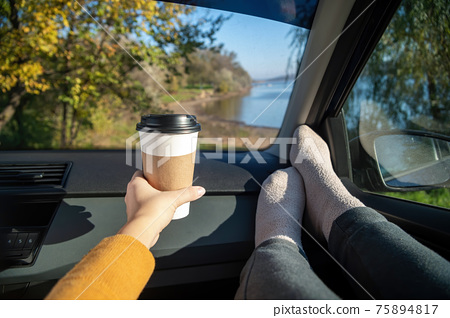Female hand holding a cup of coffee in a car, nature 75894817