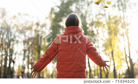 A woman with outstretched arms in forest 75894820