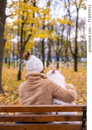 Woman with her dog in a park, autumn 75894852