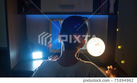 Boy using computer at night 75894962