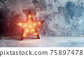 Large decorative retro star with lots of burning lights on grunge concrete background. Beautiful decor, modern design element. The loft style studio. Free space for text 75897478