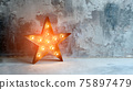 Large decorative retro star with lots of burning lights on grunge concrete background. Beautiful decor, modern design element. The loft style studio. Free space for text 75897479