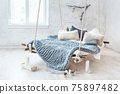 White loft interior in classic scandinavian style. Hanging bed suspended from the ceiling. Cozy large folded gray plaid, giant knit blanket, super chunky yarn, arm knitting. Trendy room design. 75897482