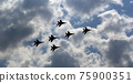 Flight of modern combat fighters on the sky background 75900351