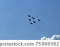 Flight of modern combat fighters on the sky background 75900362