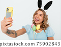 Cheerful young woman celebrating Easter makes selfie using her smart phone 75902843