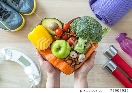Healthy lifestyle on ketogenic diet, eating clean keto food good health dietary in heart dish with aerobic body exercise, gym workout training class , weight scale and sports shoes in fitness center 75902933