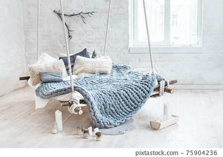 White loft interior in classic scandinavian style. Hanging bed suspended from the ceiling. Cozy large folded gray plaid, giant knit blanket, super chunky yarn, arm knitting. Trendy room design. 75904236
