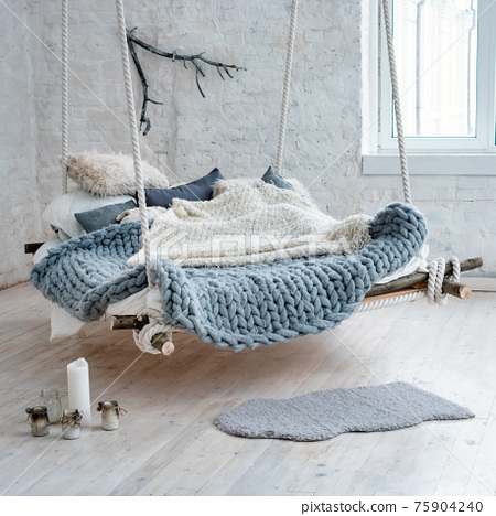 White loft interior in classic scandinavian style. Hanging bed suspended from the ceiling. Cozy large folded gray plaid, giant knit blanket, super chunky yarn, arm knitting. Trendy room design. 75904240