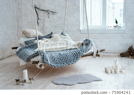 White loft interior in classic scandinavian style. Hanging bed suspended from the ceiling. Cozy large folded gray plaid, giant knit blanket, super chunky yarn, arm knitting. Trendy room design. 75904241