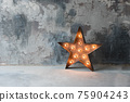 Large decorative retro star with lots of burning lights on grunge concrete background. Beautiful decor, modern design element. The loft style studio. Free space for text 75904243