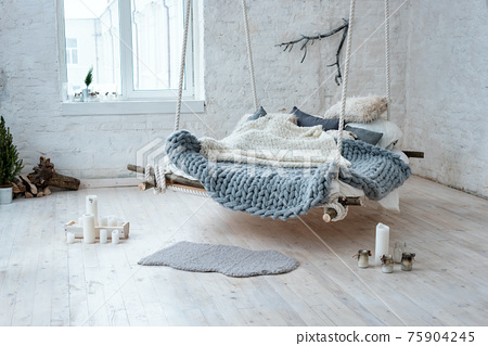 White loft interior in classic scandinavian style. Hanging bed suspended from the ceiling. Cozy large folded gray plaid, giant knit blanket, super chunky yarn, arm knitting. Trendy room design. 75904245