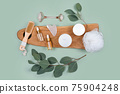 Facial roller, essential oils, cosmetic serums, face cream on green background with natural eucalyptus leaves. Beauty products, massage tools, facial skin care, spa beauty treatment concept. Flat lay 75904248