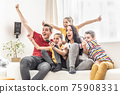 Enthusiastic family of five cheers at home watching sports on TV 75908331