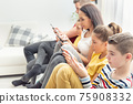 Family sitting on a sofa with all looking only into their mobile phones with zero mutual interaction 75908332