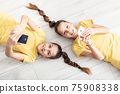 Young twin girls lying on the floor, both holding mobile phones in their hands 75908338