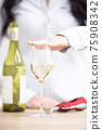 Female holding a hand above the glass of white wine with bottle and wine opener next to it 75908342