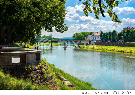 embankment of the river uzh. wonderful urban scenery in summer. view from beneath the shadow of a linden tree branches. bridge in the distance 75938557
