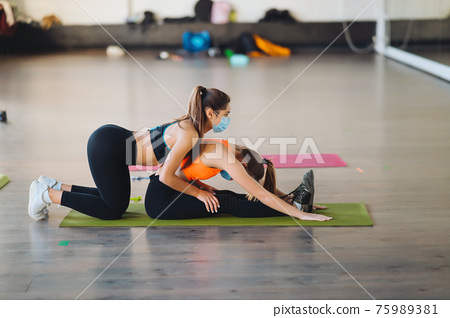 Active sportive woman stretching, young woman helping her 75989381