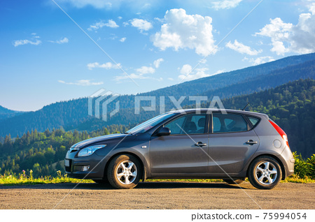mizhhirya, ukraine - AUG 08, 2020: car on the concrete parking on top of the mountain in morning light. travel countryside concept. beautiful nature scenery views in summer with fluffy clouds on the 75994054