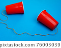Two red paper cups connected with rope on blue background, toy telephone 76003039