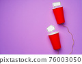 Toy telephone made of plastic cups and string with speech bubbles on purple background 76003050