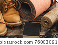 Hiking boots and rope hank on wooden board 76003091