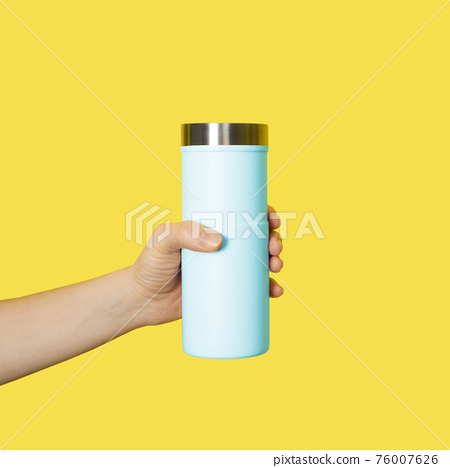 Hand holds travel mug isolated on white background. Thermo cup or tumbler in female hand 76007626