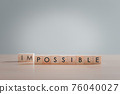 """Text """"POSSIBLE"""" on wooden block, Making possible is possible by leaving the impossible behind, Business, success, challenge, motivation, action and reaching goals, achievement and possible concept. 76040027"""