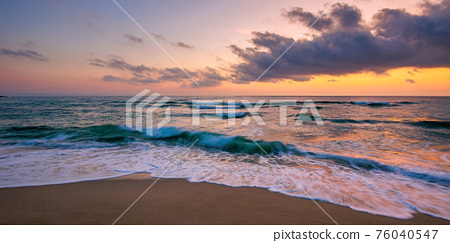 ocean beach with dramatic sky at sunrise. gorgeous vacation scenery. waves rolling on the sand in morning light 76040547