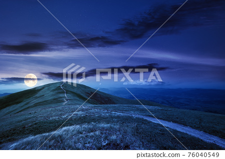 mountain landscape at night in spring. path through meadow in grass on the hill in full moon light. wonderful weather with fluffy clouds on the sky. borzhava ridge of carpathians 76040549