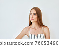 Close up portrait of pretty young woman looking aside to copy space 76053490