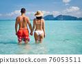 Rear view of happy couple in love enjoying warm tropical ocean water 76053511