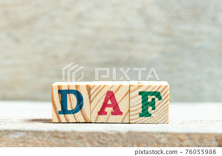 Alphabet letter block in word DAF (Abbreviation of Delivered at frontier) on wood background 76055986