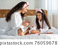Joyful mother and daughter making manicure at home 76059678