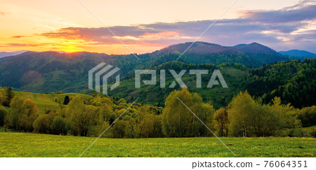 rolling rural mountain landscape at dusk. gorgeous nature scenery in spring. clouds on the sky in evening light 76064351