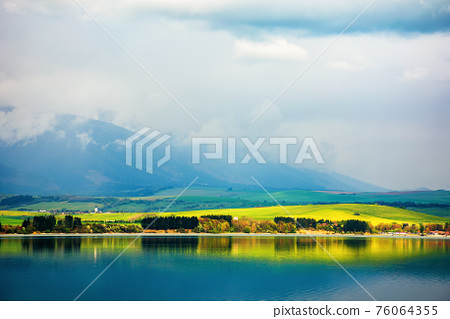 liptovska mara lake of slovakia. beautiful landscape in spring. reflection on the water surface. distant mountains in clouds 76064355