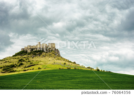 spis, slovakia - 29 APR 2019: castle ruins on the hill. grassy meadow in the foreground. popular travel destination on a cloudy day 76064356