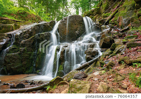 landscape with waterfall in spring. powerful water flow comes out of the rock 76064357