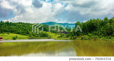 lake among mountain landscape in spring. beautiful countryside scenery with forest on the shore. clouds on the sky 76064358