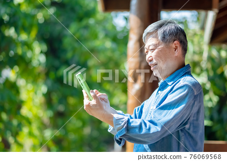 asian retired man use smartphone 76069568