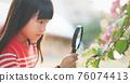 Asian girl use magnifer 76074413