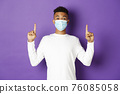 Concept of coronavirus, quarantine and lifestyle. Excited african-american guy in medical mask showing banner, pointing fingers up at copy space, standing over purple background 76085058
