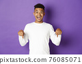 Portrait of handsome african-american guy in white sweatshirt, pointing fingers down and smiling happy, showing promo, looking amazed, standing against purple background 76085071
