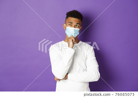 Concept of coronavirus, quarantine and lifestyle. Image of thoughtful african-american man in medical mask looking at upper left corner, thinking or making choice, standing over purple background 76085073