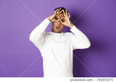Image of funny and happy african-american man in white sweatshirt, grimacing and making faces, standing over purple background 76085075